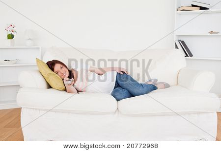 Beautiful red-haired female watching tv while lying on a sofa in the living room