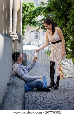 Woman gives a beggar money