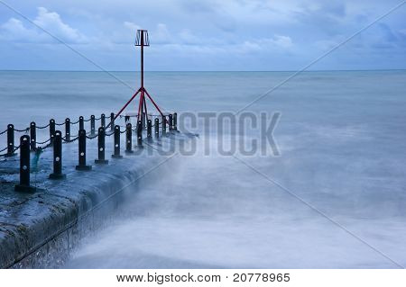 Dramatic Sea Flows Over Groyne On Beach At Wittering In England