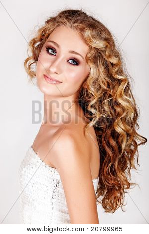 Beautiful young blonde woman with long curly hair in white fashion sequin top isolated on white background.