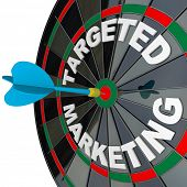 A blue dart hits a bulls-eye in the target on a dart board marked Targeted Marketing illustrating a