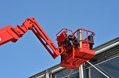 pic of cherry-picker  - red hydraulic construction cradle against the blue sky - JPG