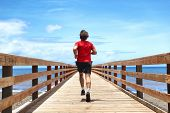 Running runner sport man jogging on beach boardwalk living active lifestyle. Workout outside person  poster