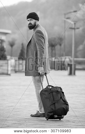 poster of Carry Travel Bag. Man Bearded Hipster Travel With Luggage Bag On Wheels. Adjust Living In New City.