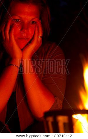 Female Is Staring Into The Fire
