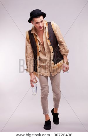 enebriated man walking on a gray background with an alcohol bottle in his hand and looking very tipsy