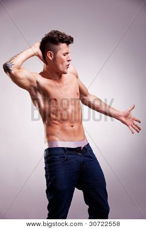 fit fashion model wearing no shirt, dancing on gray background. muscular young dancer posing