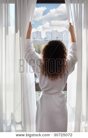 Woman dressed in white bathrobe opens curtains and looks up; woman stands back to camera