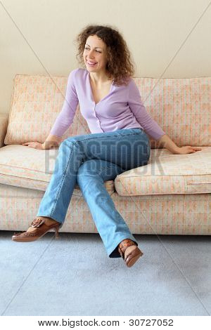 Beautiful smiling woman sits on couch in simple comfortable room