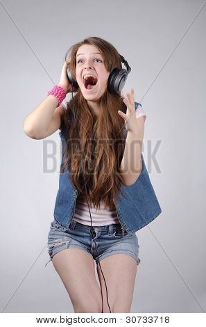 funny grimacing young woman with long hairs and headphones in jeanswear standing isolated on grey