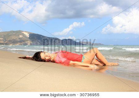 Woman in bikini wearing a red shirt relax on the beach