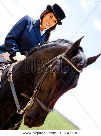 Elegant woman horseback riding outdoors and smiling