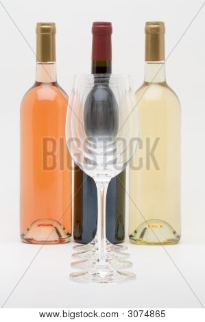 Red White And Rose Wine Bottles With Glasses In Front