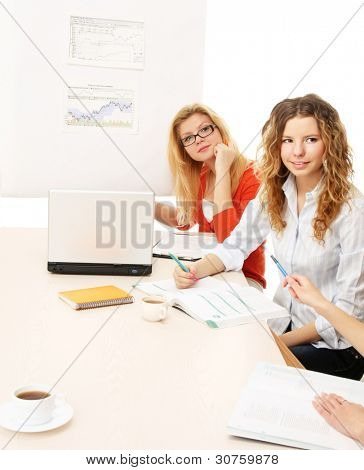 A group of working women is sitting  on the table - on white background
