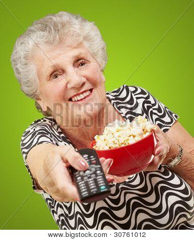 Portrait of senior Woman holding Popcorn Schüssel und Kanal tv gegenüber dem grünen Hintergrund ändern