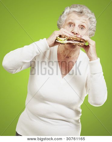 senior woman eating a healthy sandwich against a green background