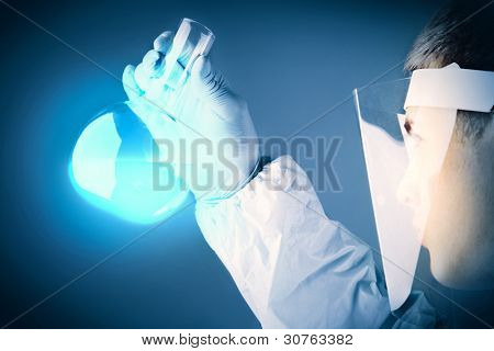 Young scientist in transparent protective mask looking at blue substance poured in a flask