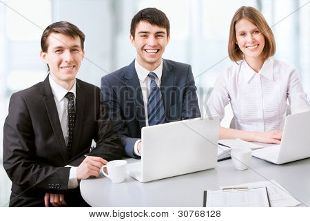 Three business colleagues working together, looking at camera, smiling