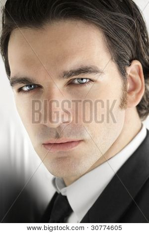 Portrait of a sexy upscale male model with bright blue eyes in elegant business attire against a cool modern bright metallic background