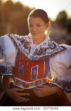 Keeping tradition alive: young woman in a richly decorated ceremonial folk dress/regional costume (Kyjov folk costume, Southern Moravia, Czech Republic)
