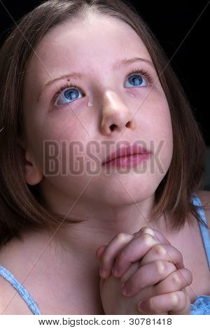 Young girl praying and crying - closeup portrait