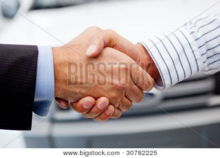 Business handshake to close the deal after buying a car