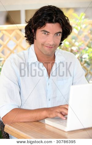 portrait of handsome dark-haired man working on laptop