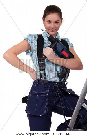cute teenage apprentice holding electric drill with leg resting on ladder