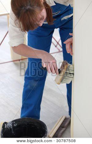 Woman using a wallpaper brush