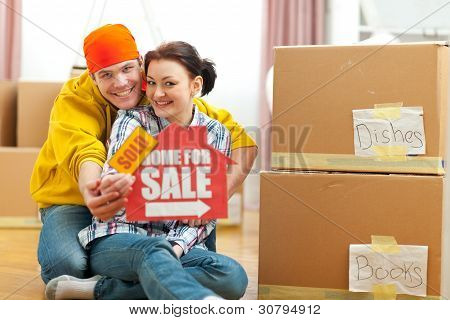 Hugging Young Couple Showing Home For Sale Sign With Sold Sticke