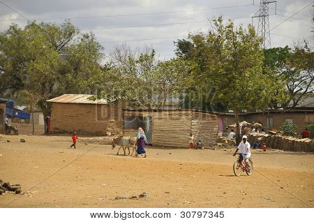 Unidentified Masai people walking through the Arusha village