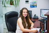 Young Caucasian Business Lady Is Looking At Camera And Smiling While Sitting On Her Workplace In Off poster