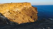 Top View Of Coastal Cliff With Blue Sea At Sunset. Shot. Beautiful View Of Golden Sunset Light On Ro poster