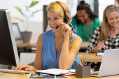 Front view of happy Caucasian female customer service executive talking on headset and working on co poster