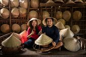 Asian Couple Traveler Craftsman Making The Traditional Vietnam Hat In The Old Traditional House In A poster