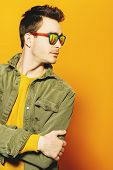 A portrait of a fashionable young man posing in the studio over the yellow background. Casual fashio poster
