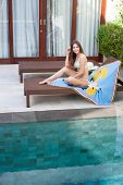 Beautiful Sexy Young Smiling Woman With Long Hair In A Bikini Sitting On A Lounger Covered With Blue poster