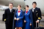 stock photo of work crew  - Airplane cabin crew standing at the airport with bags - JPG