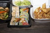 Sushi, Wontons And Sliced Avocado In Carryout Boxes poster