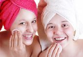 picture of freckle face  - Portrait of two teenage girls are cleaning their faces with cotton pads - JPG