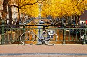 Bike On A Bridge, Canal Ring Of Amsterdam, Netherlands At Fall poster