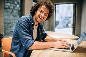 Portrait Of Happy Young Man With Curly Hair Using Laptop For Working And Browsing Online. Smart Cauc poster