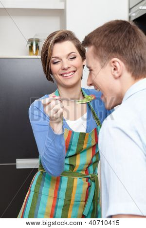 Woman offers her husband to taste salad in the modern comfortable kitchen