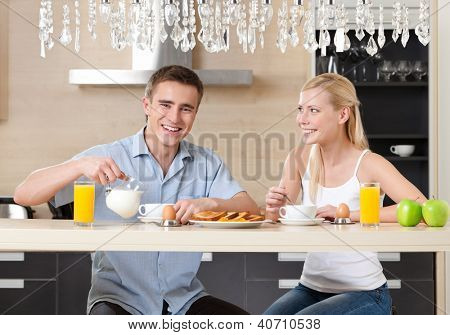 Married couple has a snack in the modern comfortable kitchen