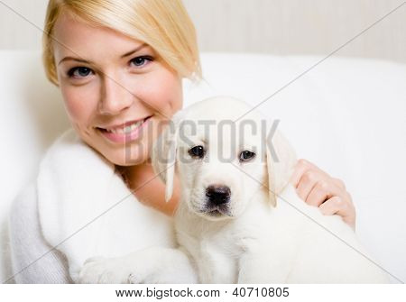White labrador puppy sitting on the hands of woman