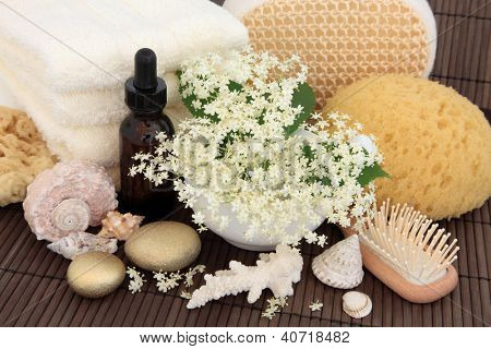 Elderflower flowers with leaf sprigs, aromatherapy essential oil bottle, gold spa stones, cream towels, exfoliating scrub, natural sponges and brush over bamboo.