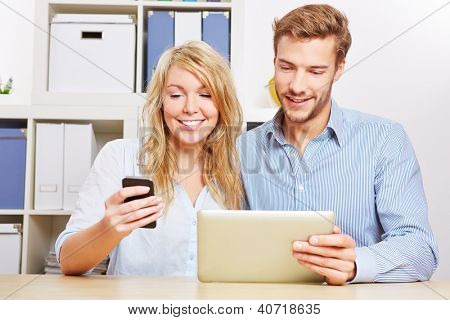 Couple synchronising a smartphone and tablet computer in the living room