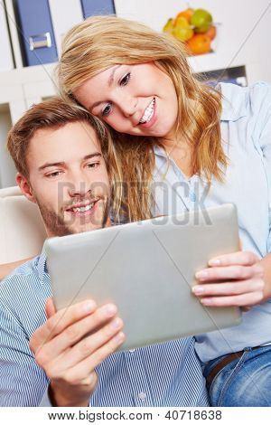 Happy couple watching movie as online stream on a tablet computer