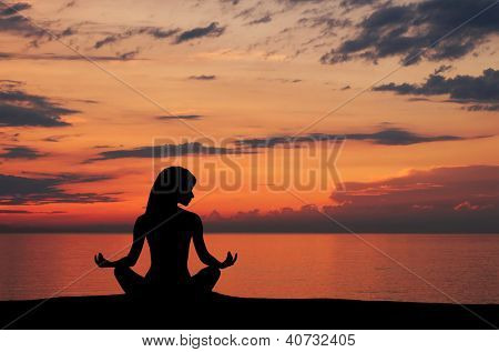 Silhouette of young woman doing yoga exercise over the sunset background