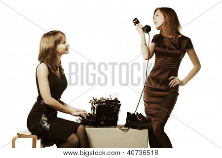 Two young women with retro typewriter and phone
